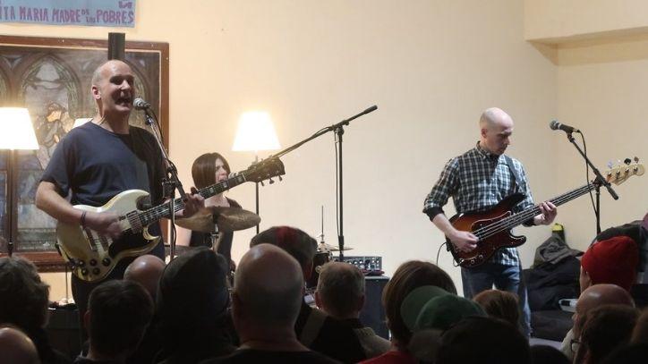 Zwei Männer und eine Frau am Schlagzeug treten vor Publikum auf.