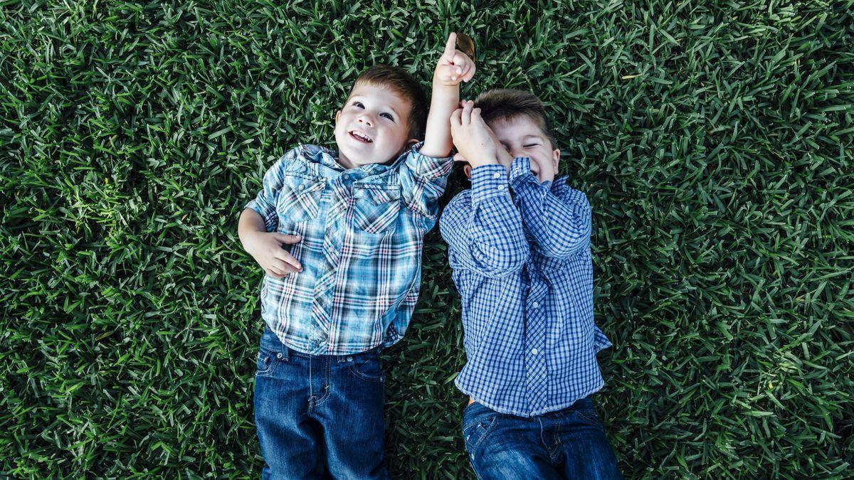 Zwei Jungen spielen zusammen im Gras.