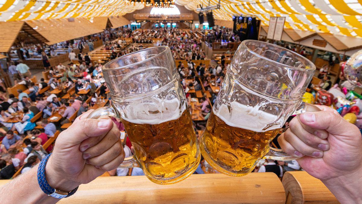 Besucher des Gäubodenvolksfestes 2019 stoßen in einem Festzelt mit Bierkrügen an.