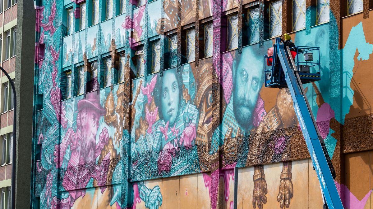 """Künstler """"Won ABC"""" malt in München-Giesing ein Bild mit den fotorealistischen Köpfen von Kurt Eisner (l-r), Sarah Sonja Rabinowitz und Erich Mühsam."""