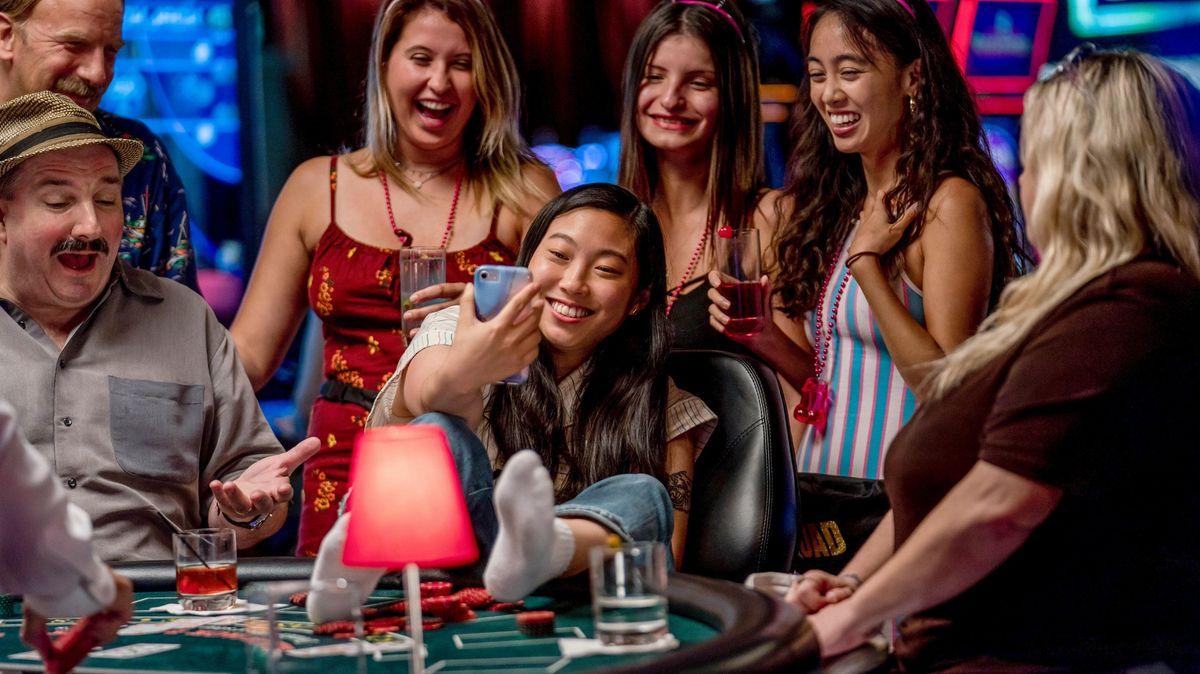 Vier Junge Frauen sitzen an einem Pokertisch und machen ein Selfie.