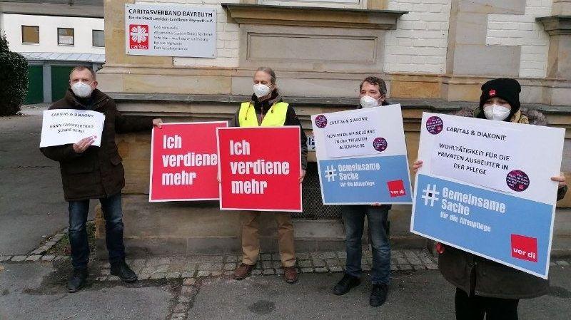 """Vier Personen halten Protest-Schilder von Verdi in die Höhe. Zu lesen ist unter anderem """"Ich verdiene mehr""""."""