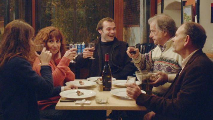 Fünf Personen sitzen an einem Tisch und essen und trinken.