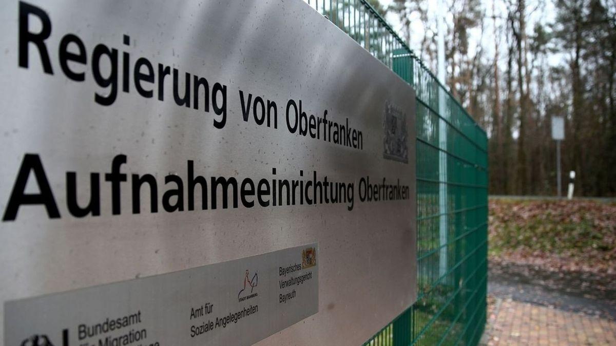 """Ein Schild mit der Aufschrift """"Regierung von Oberfranken, Aufnahmeeinrichtung"""" ist an einem grünen Zaun befestigt."""
