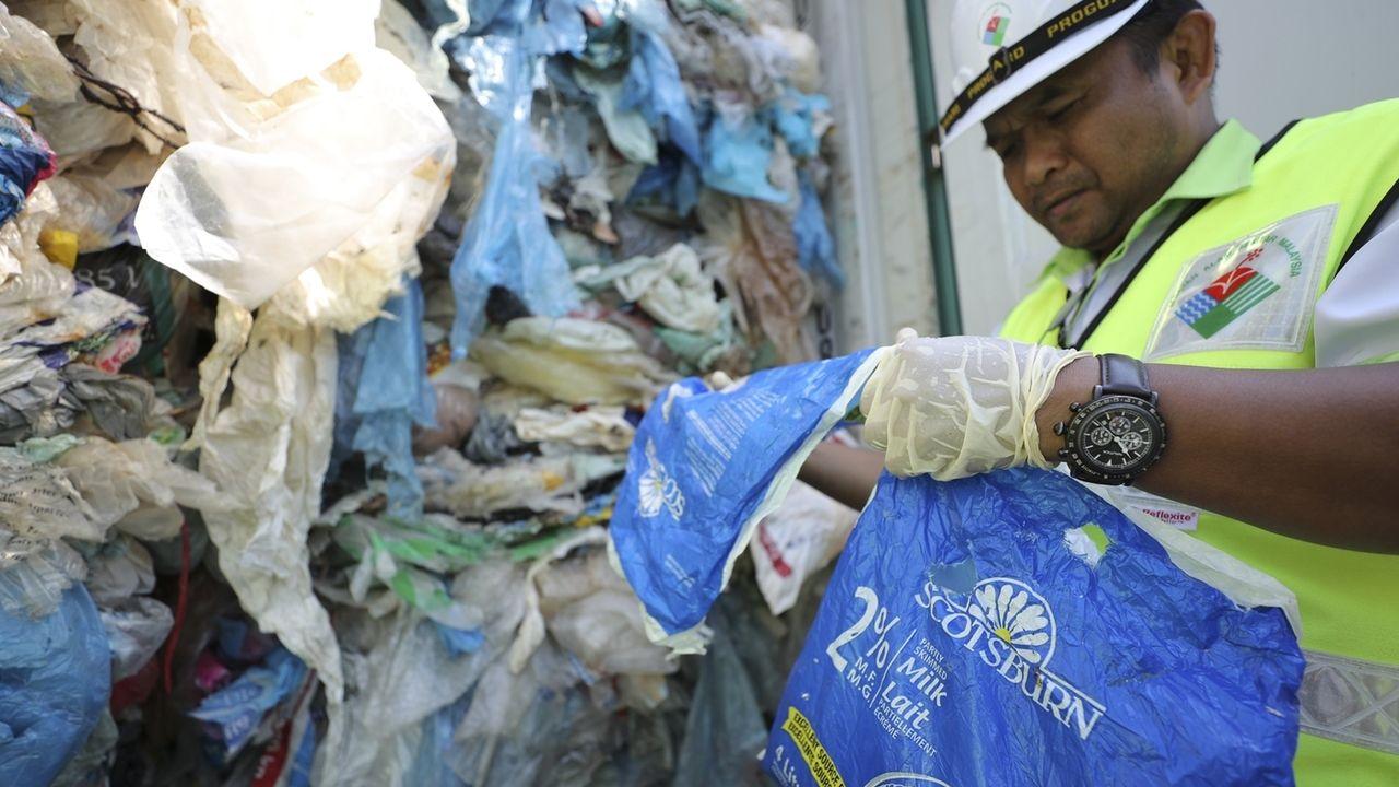 Ein Beamter des Umweltministeriums von Malaysia untersuchen einen Container voller nicht recycelbarer Kunststoffe, der von den Behörden festgesetzt wurde.