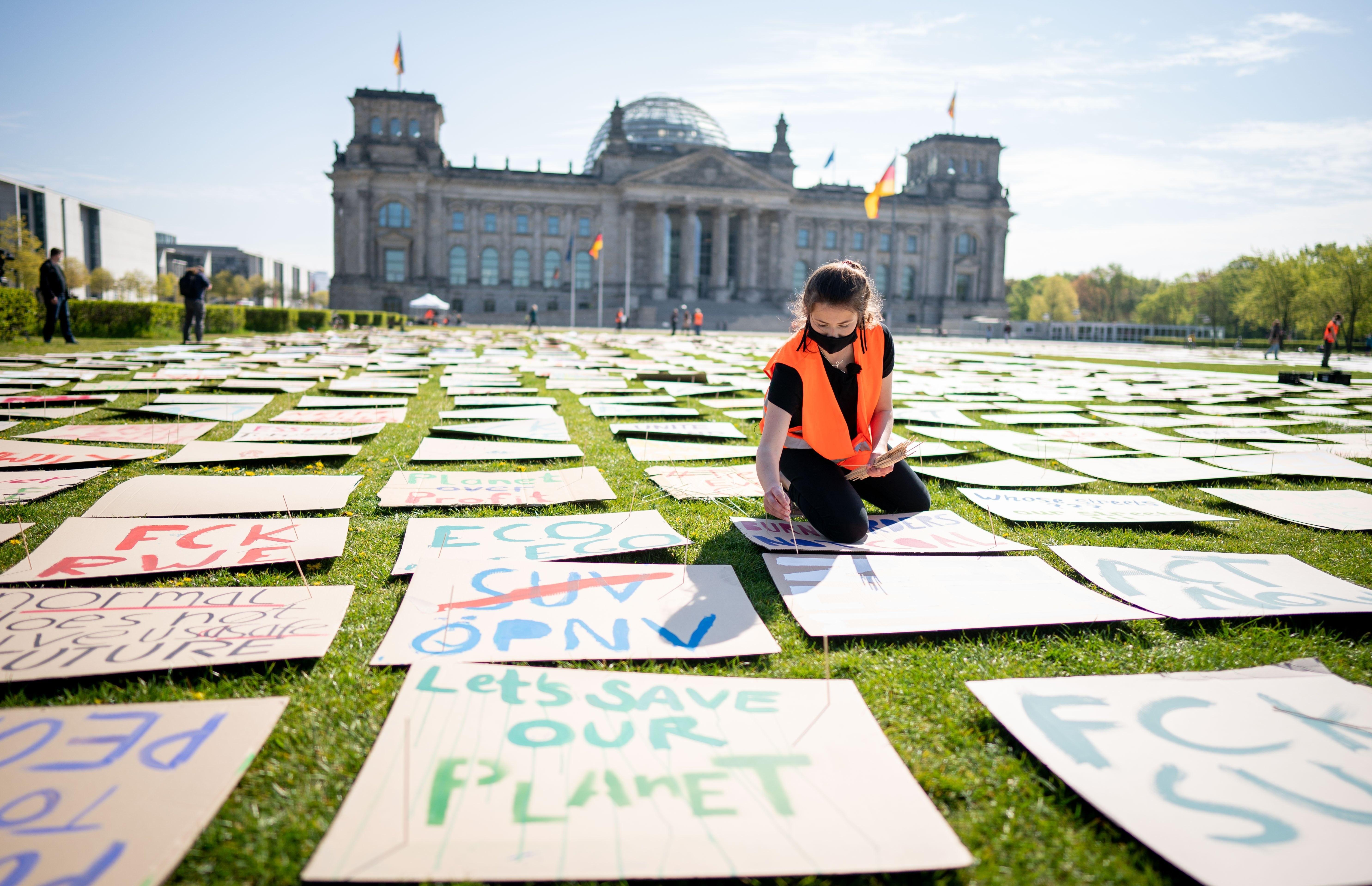 Luisa Neubauer von Fridays for Future legt für den alternativen Klimastreik Protestplakate für den Klimaschutz auf der Reichstagswiese aus.