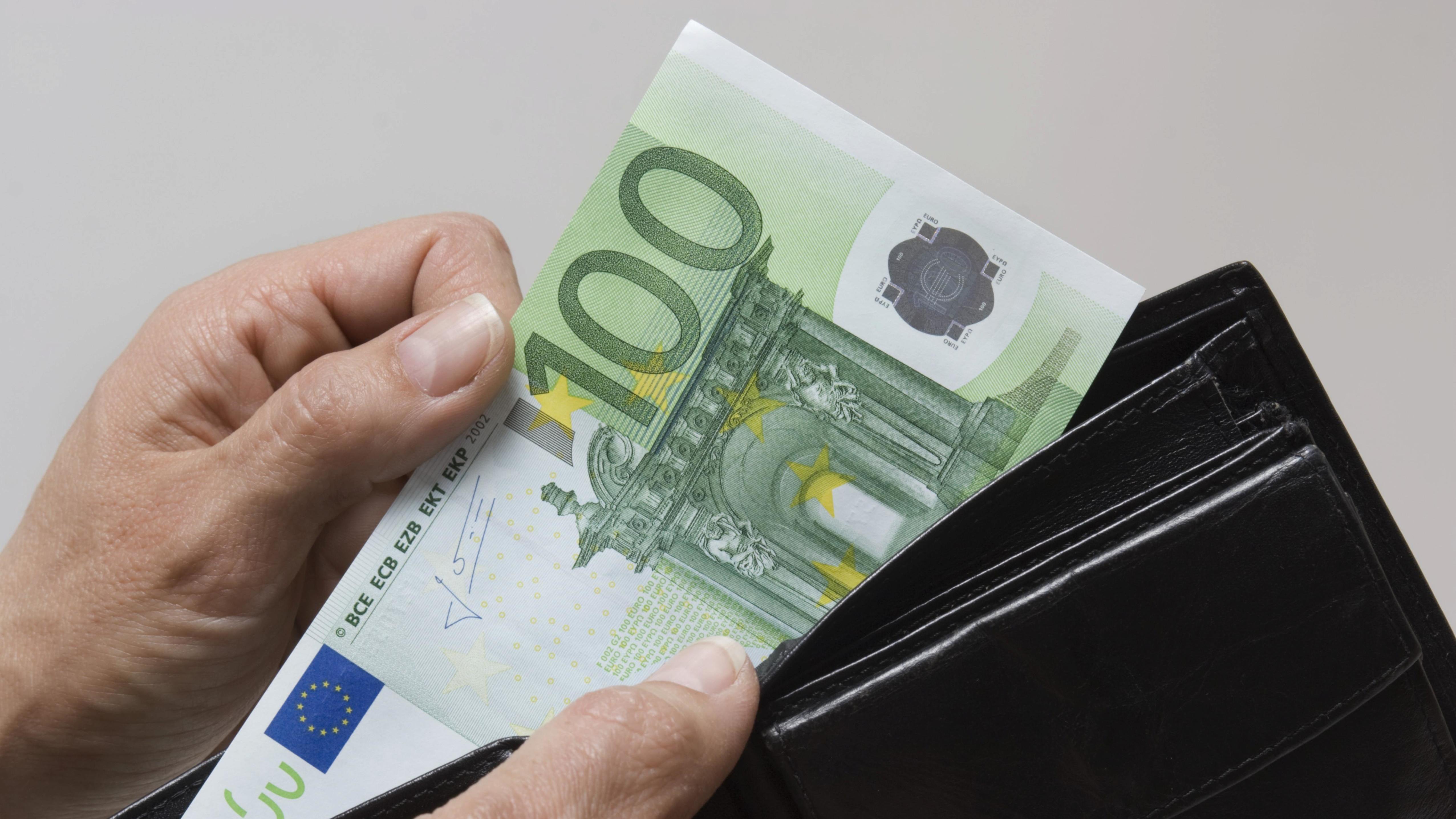 Ein Mann nimmt Geld aus einer Geldbörse.