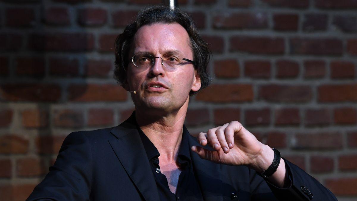 Medienwissenschaftler und Autor Bernhard Pörksen sitzt vor einer Backsteinmauer