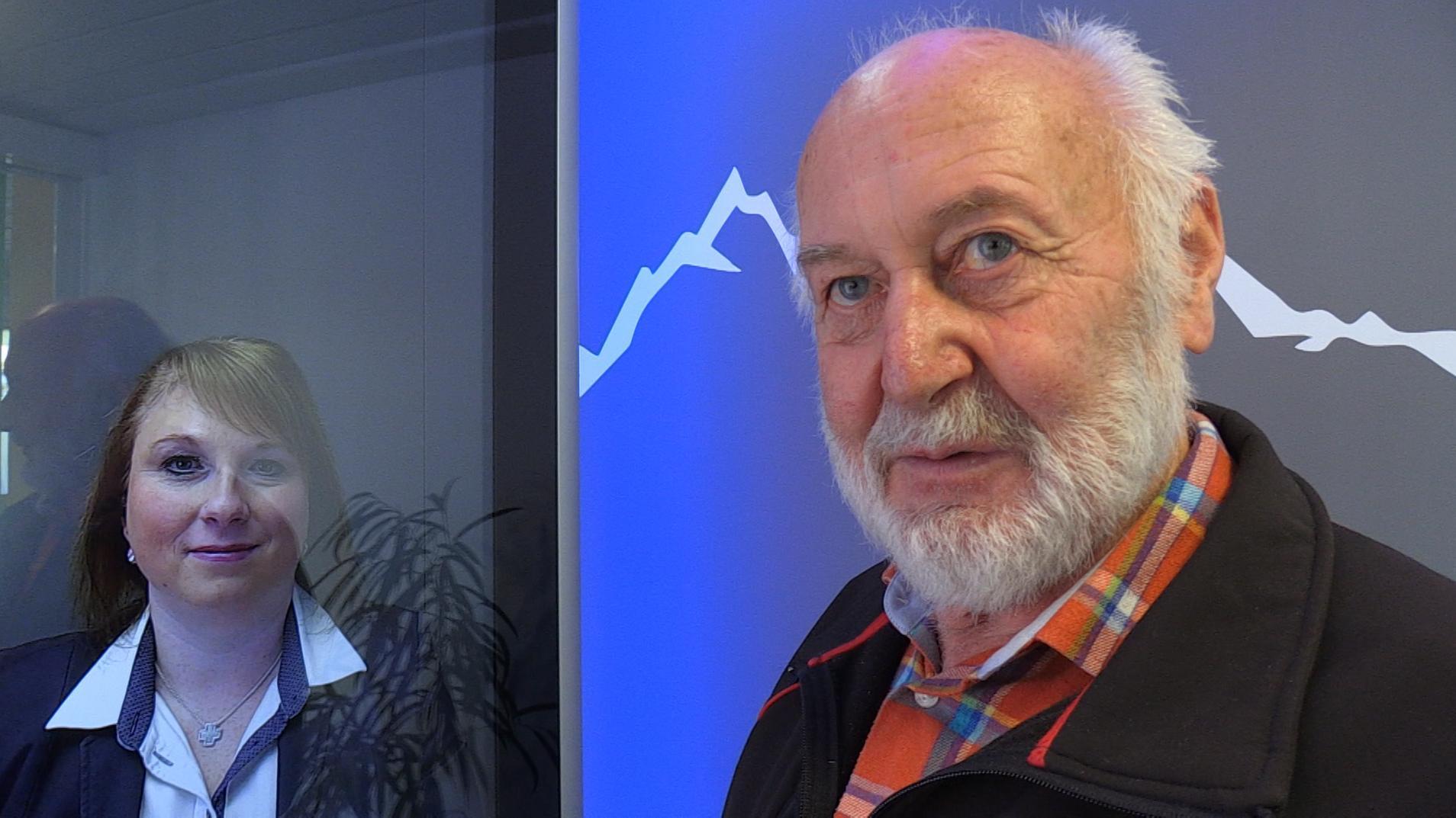Hans Hartmann steht neben dem Video-Bildschirm, auf dem die Beraterin Kerstin Mayr zu sehen