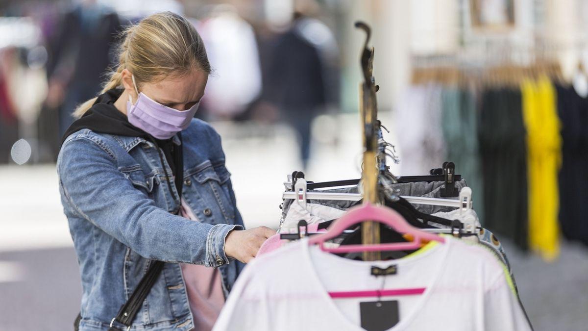 Eine Frau mit Maske schaut sich Kleider an (Symbolbild)