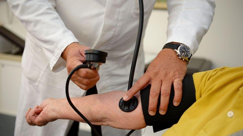 Symbolbild: Ein Arzt misst bei einem Patienten Blutdruck