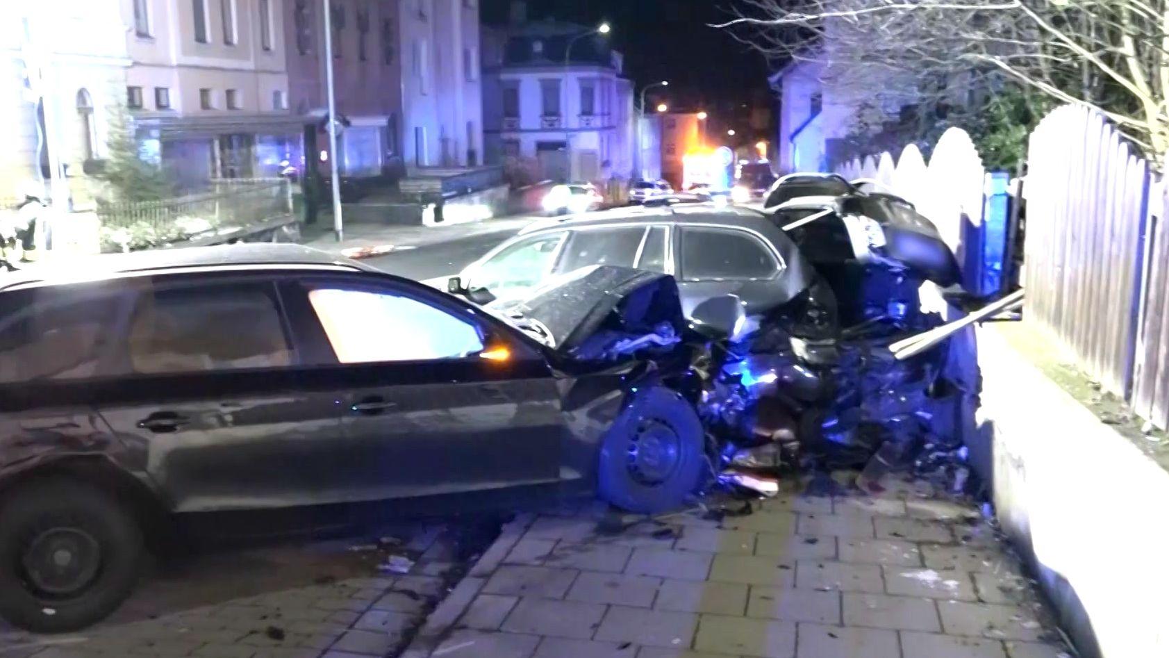 Zwei schwer beschädigte Autos stehen auf einem Gehweg.