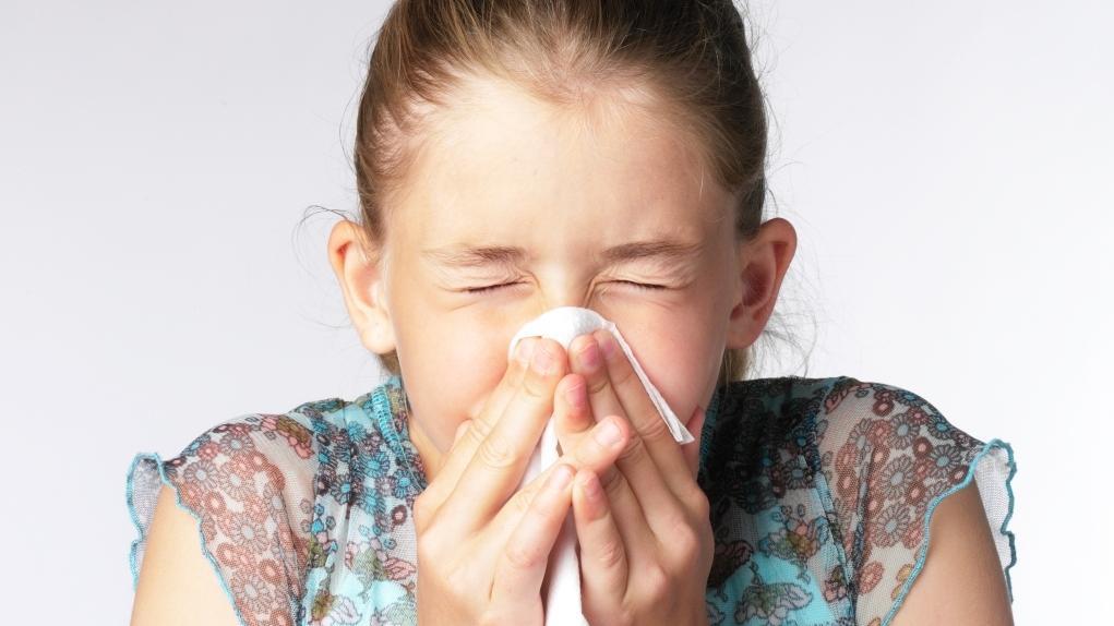 Mädchen niest in ein Taschentuch