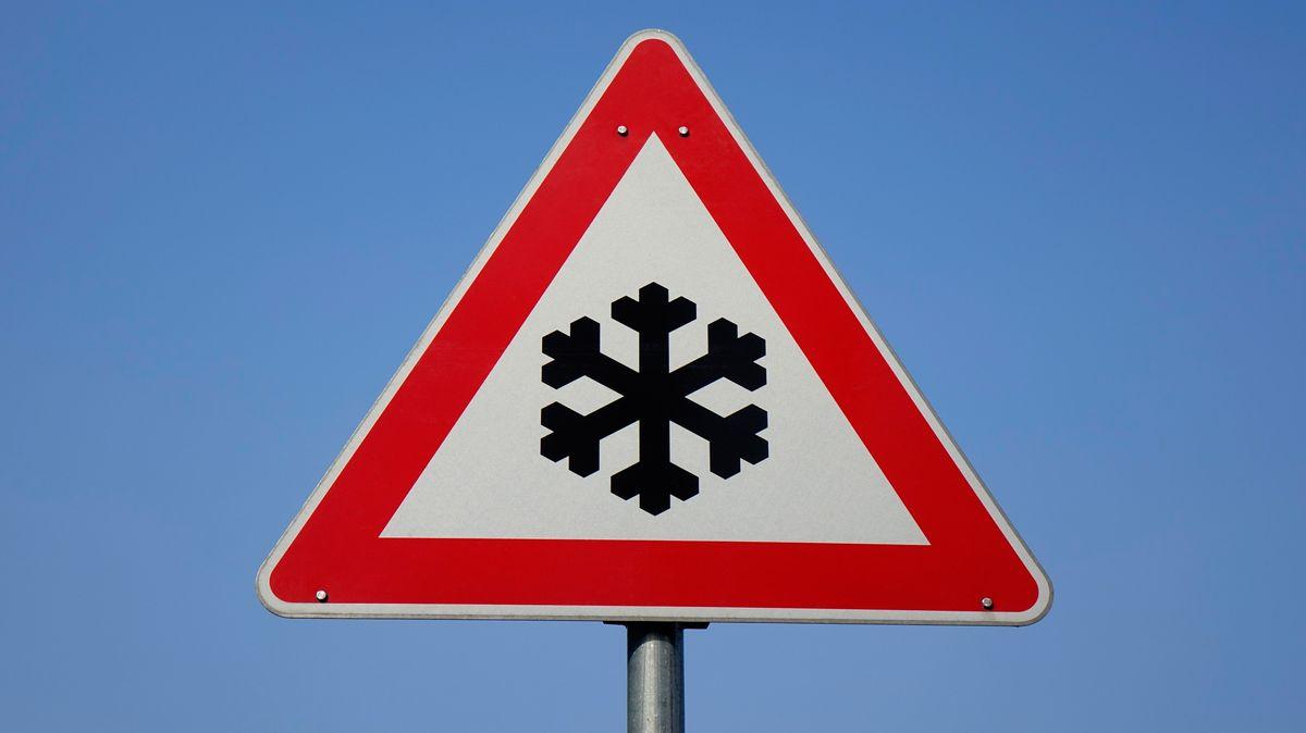 Schneeflocken-Symbol auf Verkehrsschild warnt vor Glätte