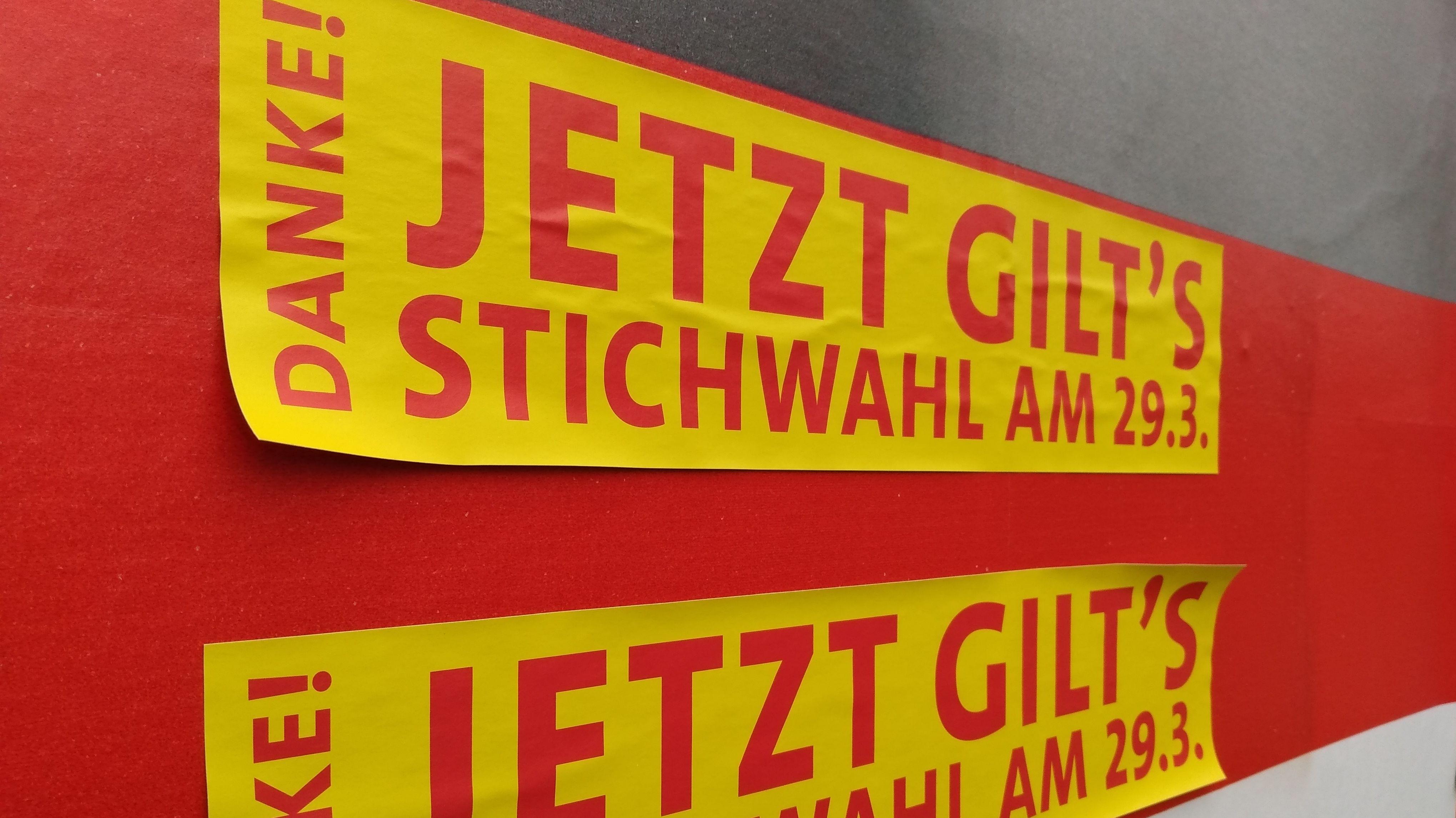 """Gelber Plakataufkleber mit der Aufschrift """"Jetzt gilt's - Stichwahl am 29.3."""""""