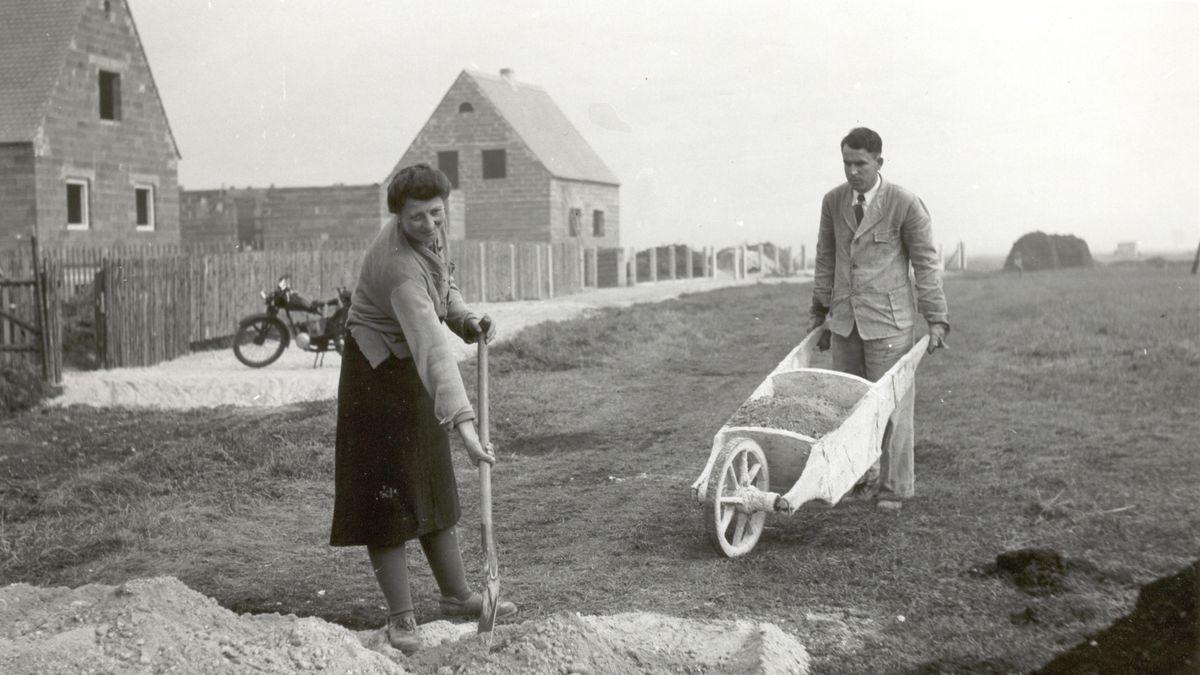 Mondscheinsiedlung: Die Frau schaufelt, der Mann fährt mit der hölzernen Schubkarre über die Baustelle.