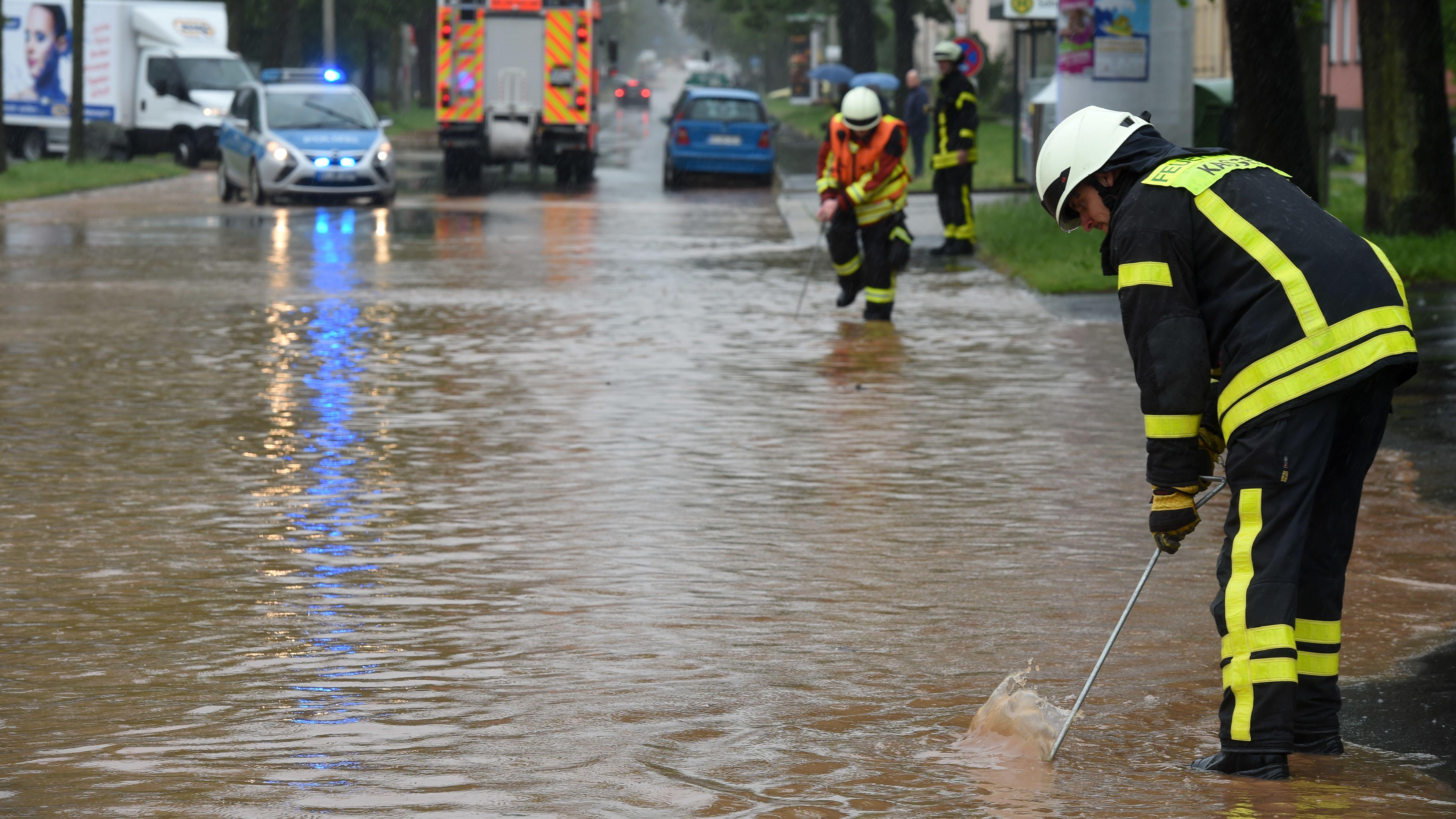 Feuerwehrleute suchen mit Eisenstangen in einer überfluteten Straße nach dem Gullydeckel