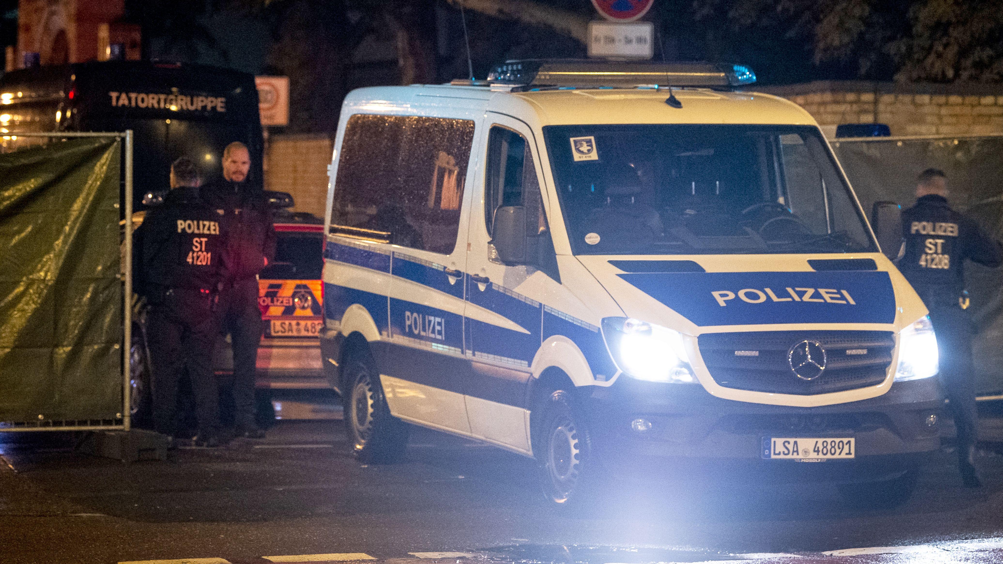 Halle: Ein Einsatzfahrzeug steht vor einem Gitter mit Sichtschutz nahe dem Tatort an der Synagoge