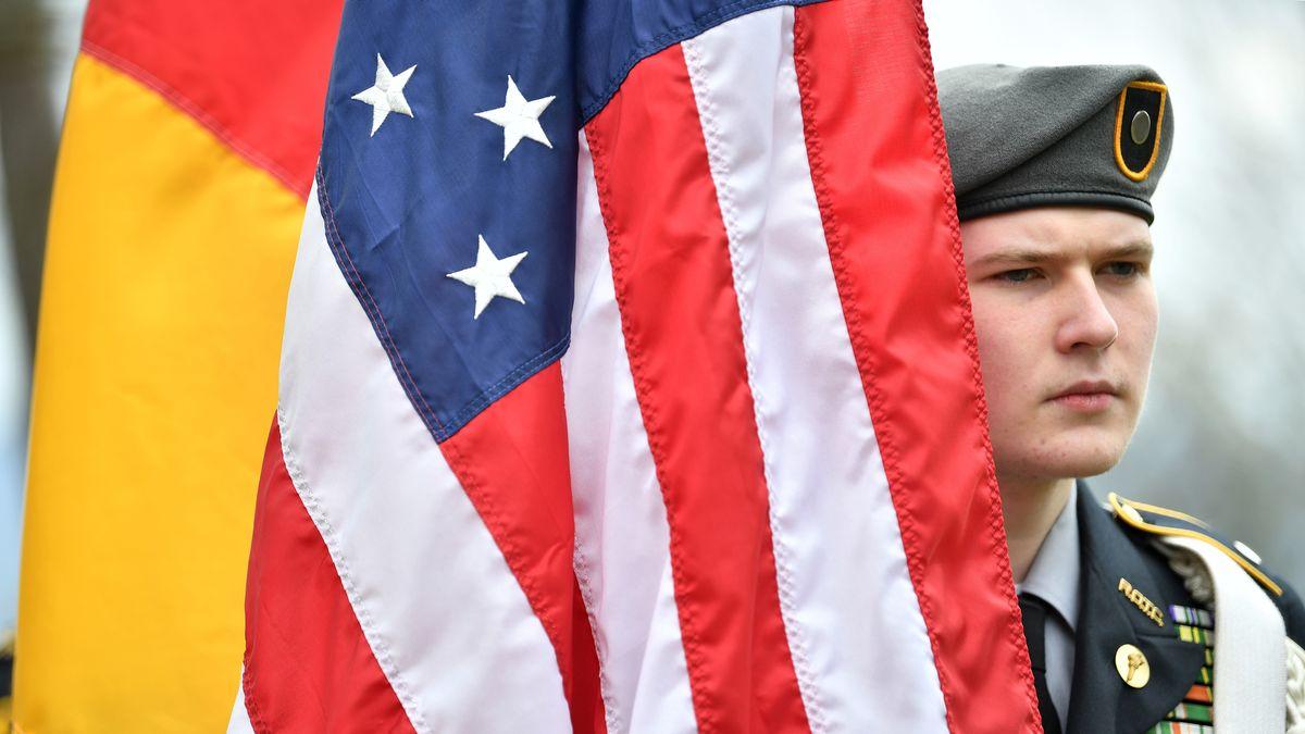 Deutsche und Amerikanische Flagge, daneben steht ein US-Soldat