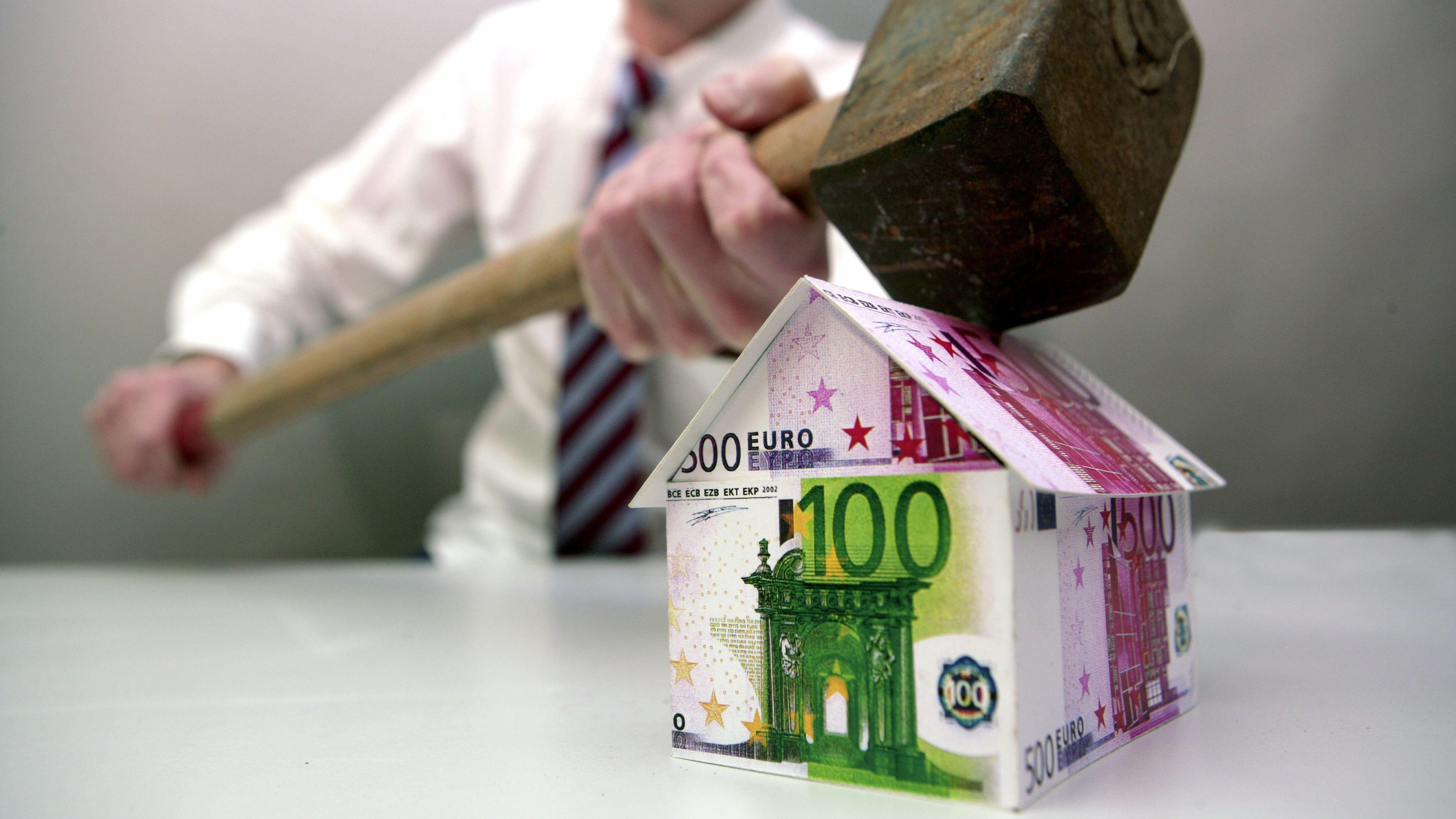 Mann haut mit einem Riesenhammer auf ein Haus aus Eurogeldscheinen