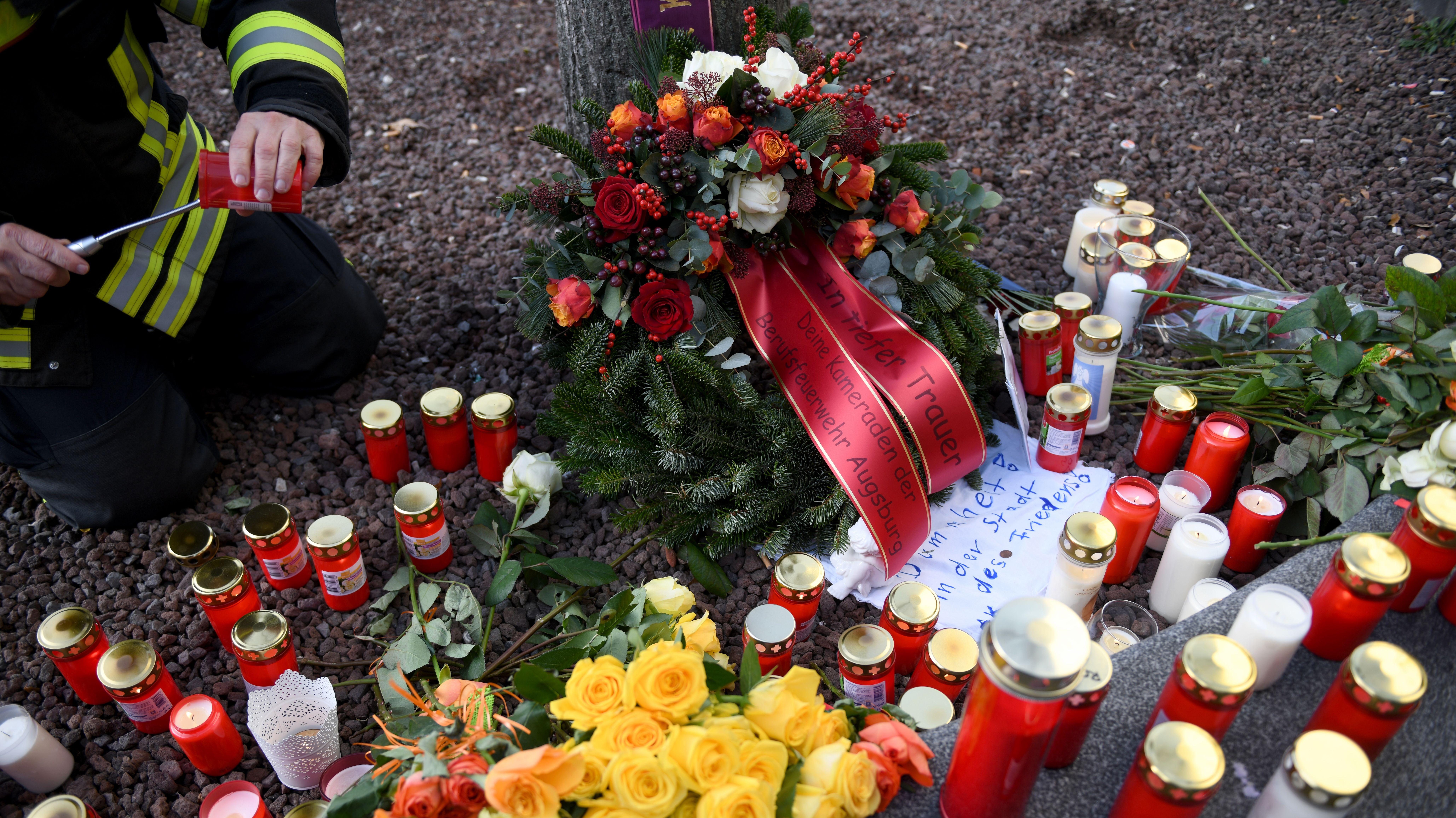 Am Augsburger Königsplatz zündet ein Feuerwehrmann eine Kerze an