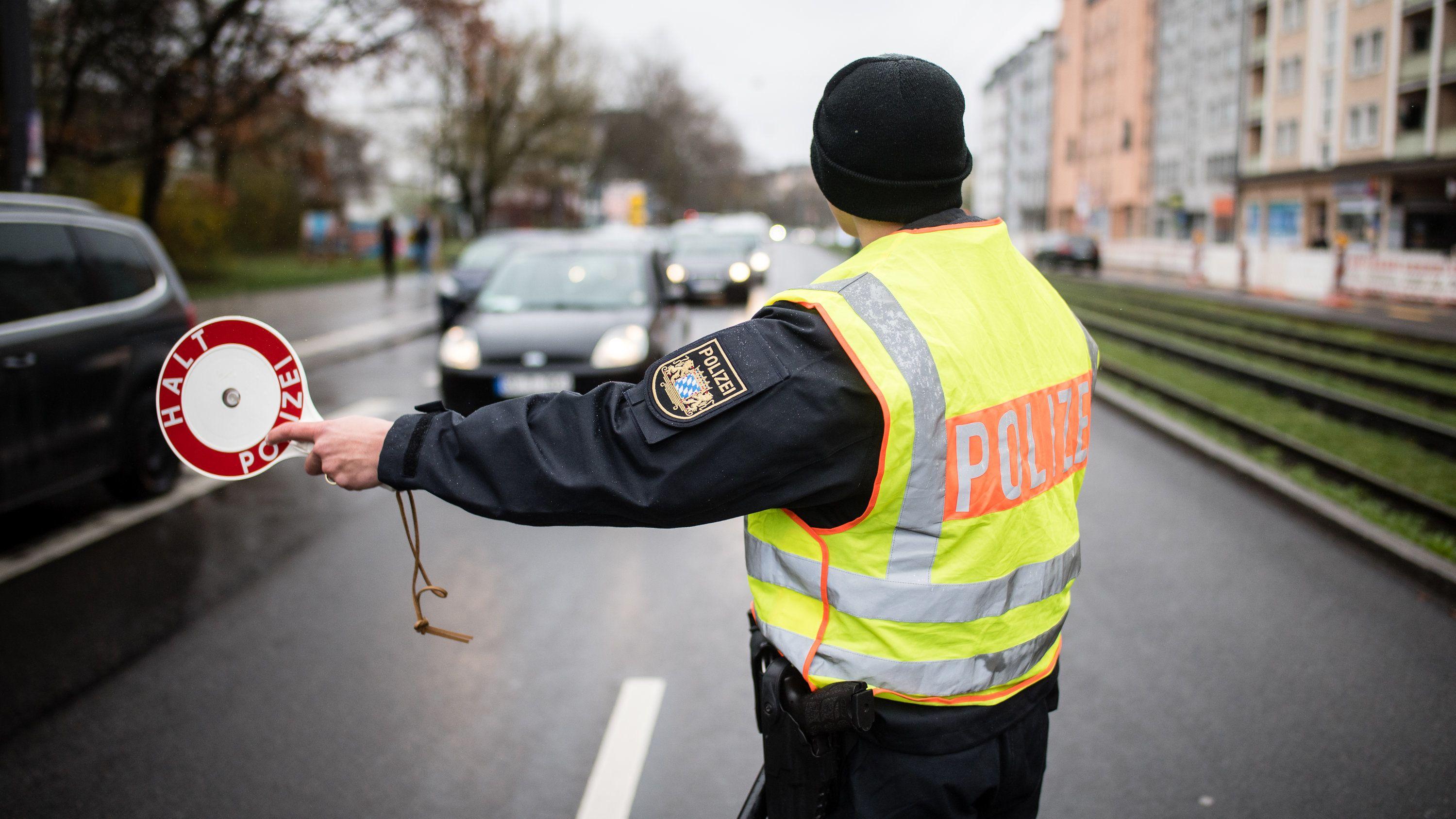 Ausgangsbeschränkungen in München: Ein Polizist stoppt an einer Kontrollstelle ein Fahrzeug mit seiner Kelle.