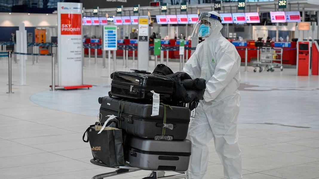 Mann im Schutzanzug mit Kofferkuli in Flughafenhalle