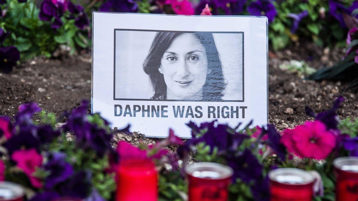 Ein Bild von Daphne Caruana Galizia steht inmitten von Blumen, davor Grablichter