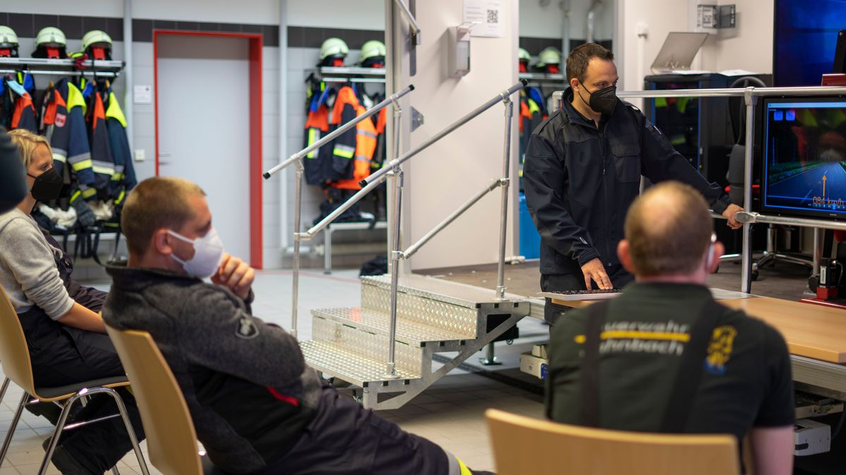 Feuerwehrkräfte werten nach der Übungsfahrt im Simulator Details und Fahrmanöver in der Gruppe vor dem Monitor aus.