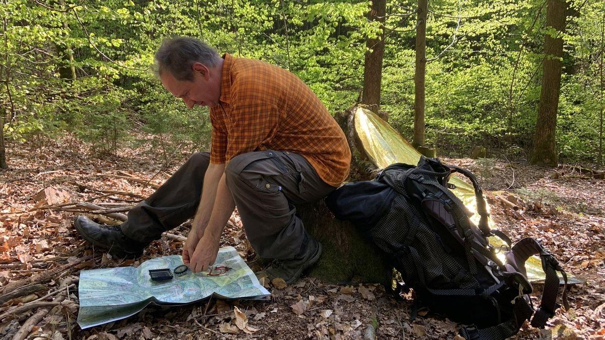 Ein Mann sitzt mit Karte und Kompass auf einem Waldboden