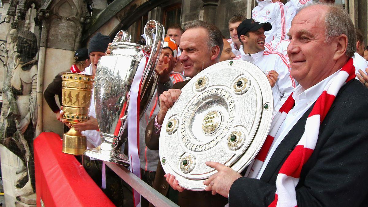 FC Bayern auf dem Münchner Rathausbalkon mit Meisterschale, DFB- und Champions-League-Pokal