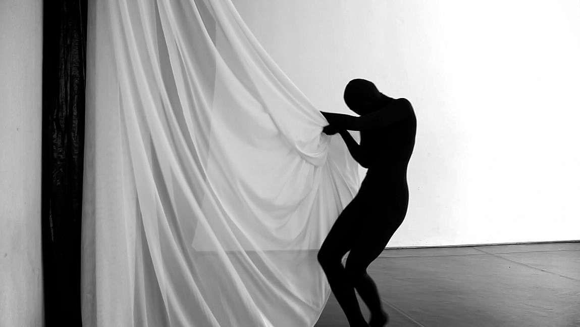 """Aus dem Eröffnungsfilm """"The Euphoria of Being"""": Kontur einer Tänzerin mit einem weißen Vorhang"""