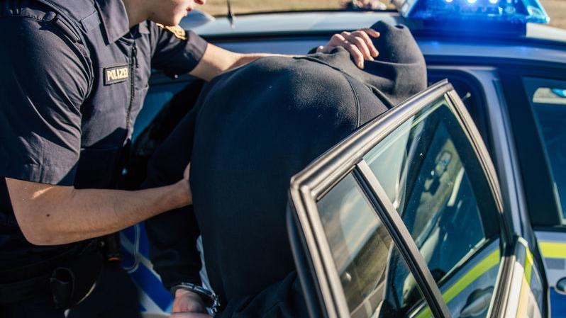 Symbolbild: Polizei hilft festgenommenen Mann beim Einsteigen ins Polizeifahrzeug. Mann trägt Kapuzenpulli und ist im Polizeigriff.