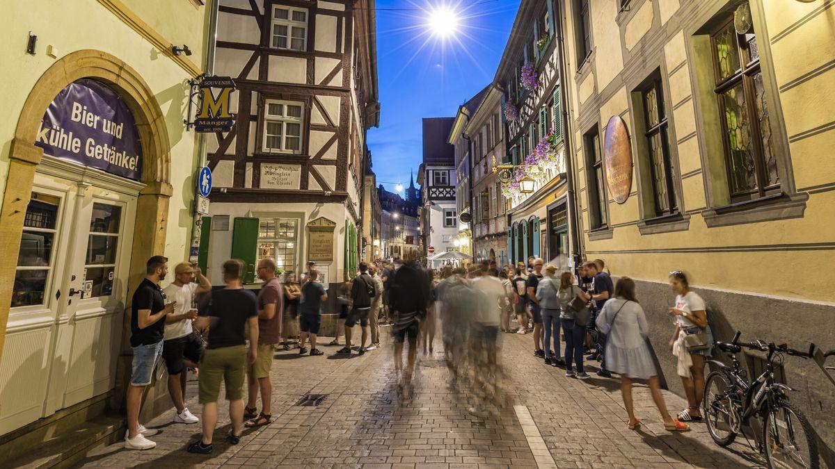 Menschen stehen am frühen Abend im Bamberger Kneipenviertel, reden und trinken Bier