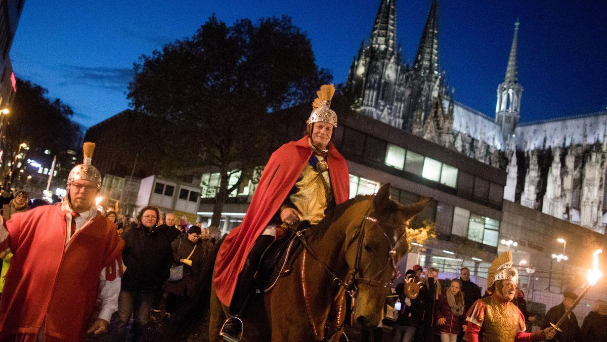 """ARCHIV - 10.11.2017, Nordrhein-Westfalen, Köln: Der """"Heilige Sankt Martin"""" reitet bei einem Martinszug am Dom vorbei."""