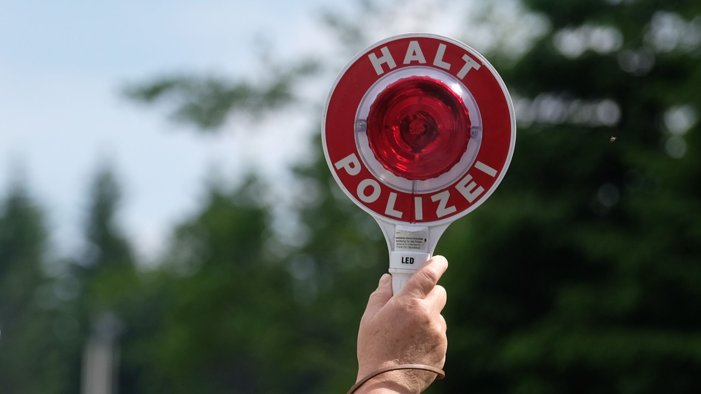 Ein Polizist hält eine rote Winkerkelle in die Höhe