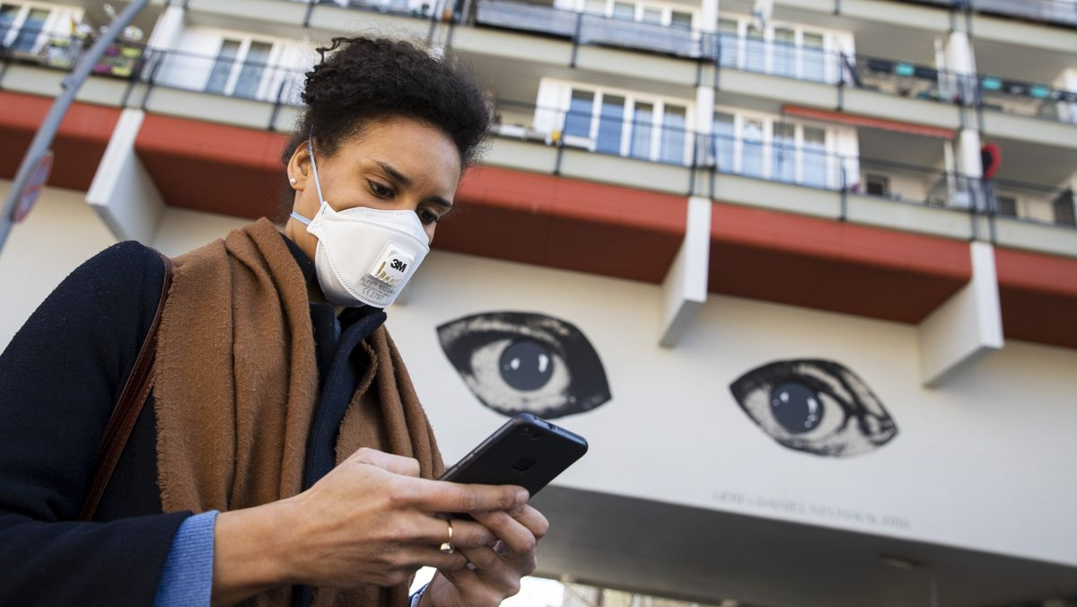 A young woman wearing a face masking is typing on her cellphone. In the background, street art of two big eyes staring at the viewer