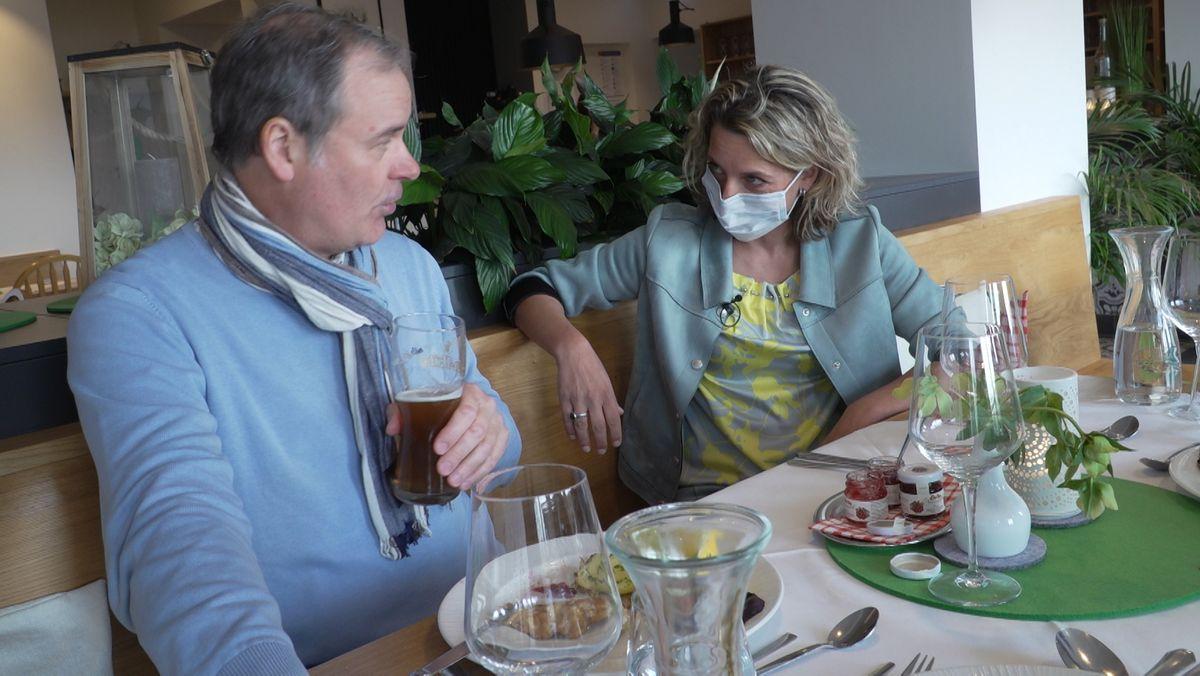 Die Restaurantchefin (Stefanie Nömeier) beruhigt den Gast (Andreas Kern) , indem sie sich zu ihm setzt und verständnisvoll mit ihm redet. Das Mittagessen , Schnitzel und Kartoffelsalat, ist fast aufgegessen
