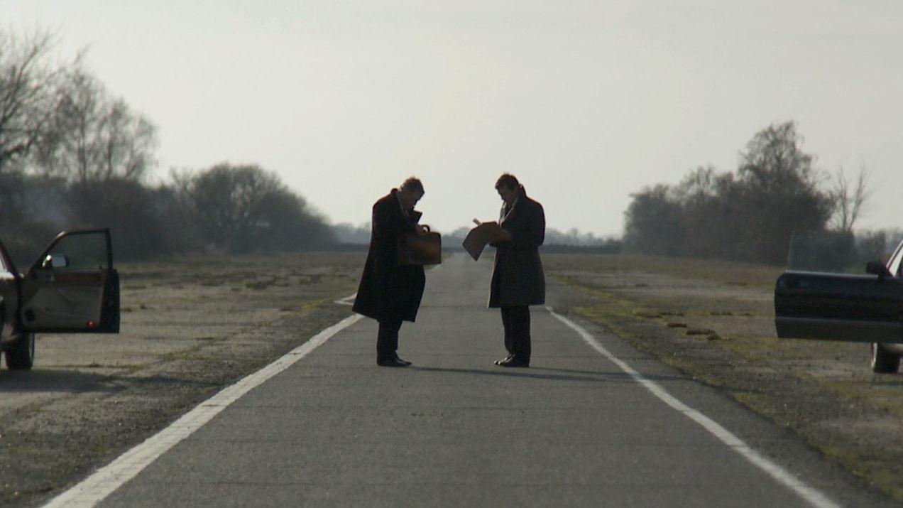 Zwei Männer auf einer abgelegenen Straße zwischen zwei Autos mit offenen Türen