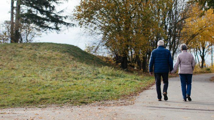 Ein älteres Pärchen geht in einer Herbstlandschaft spazieren.