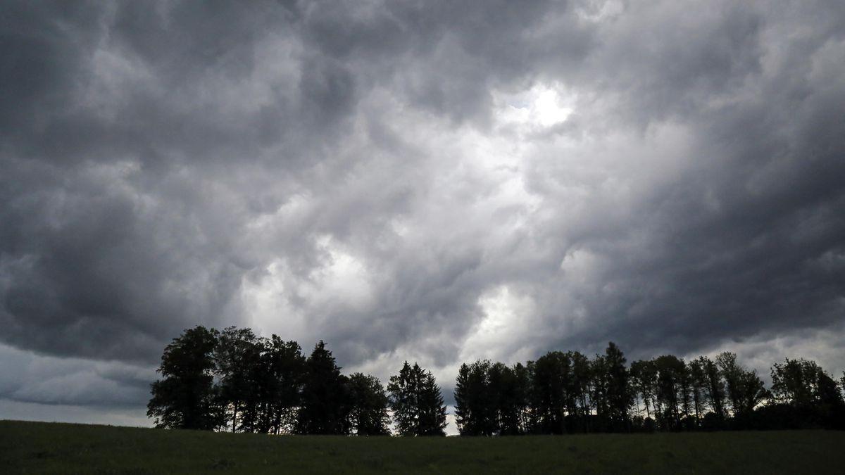 Gewitterwolken über Feld und Baumreihe in Beuerberg, Oberbayern.