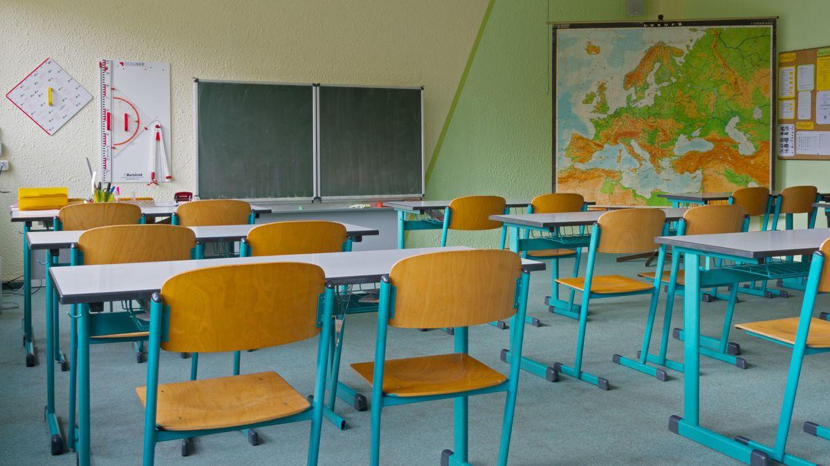Symbolbild: Leeres Klassenzimmer mit Tischen und Stühlen und einer Europa-Wandkarte