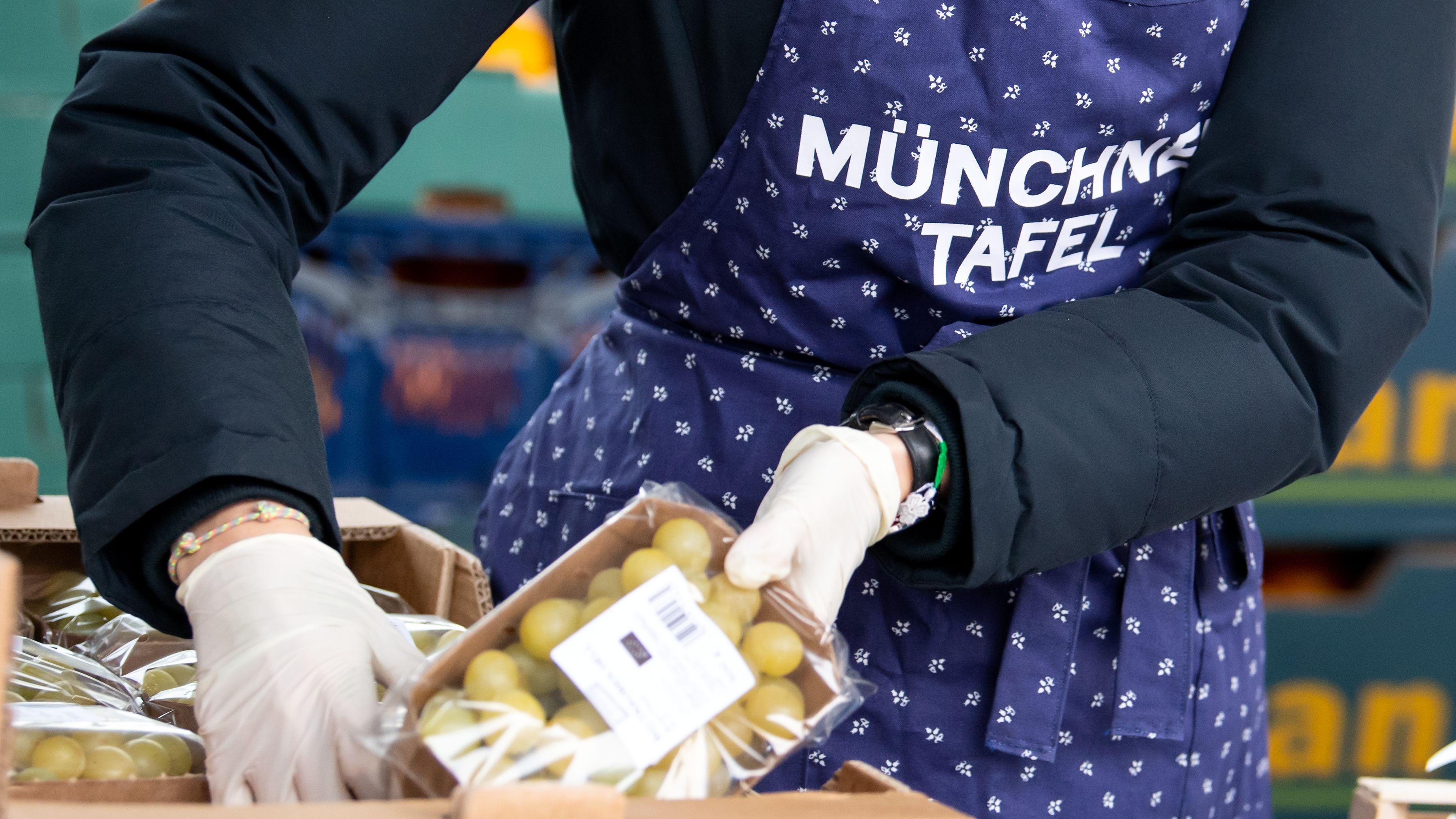 Ehrenamtliche Helfer der Münchner Tafel sortieren an der Ausgabestelle am Großmarkt Lebensmittel für die Gäste