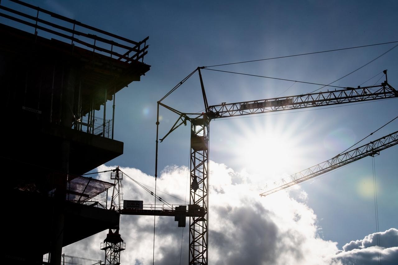08.02.2021, Bayern, München: Sonnenschein hinter Baukränen an einer Baustelle. (zu dpa Baugenehmigungen für Wohnungen auf höchstem Stand seit 22 Jahren) Foto: Matthias Balk/dpa +++ dpa-Bildfunk +++