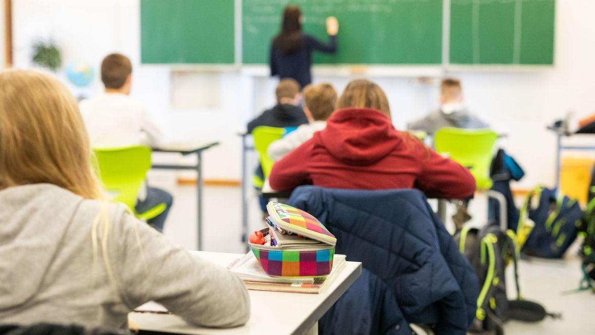 Blick in ein Klassenzimmer: Mehrere Kinder sitzen an ihren Plätzen während eine Lehrerin etwas auf die Tafel schreibt.