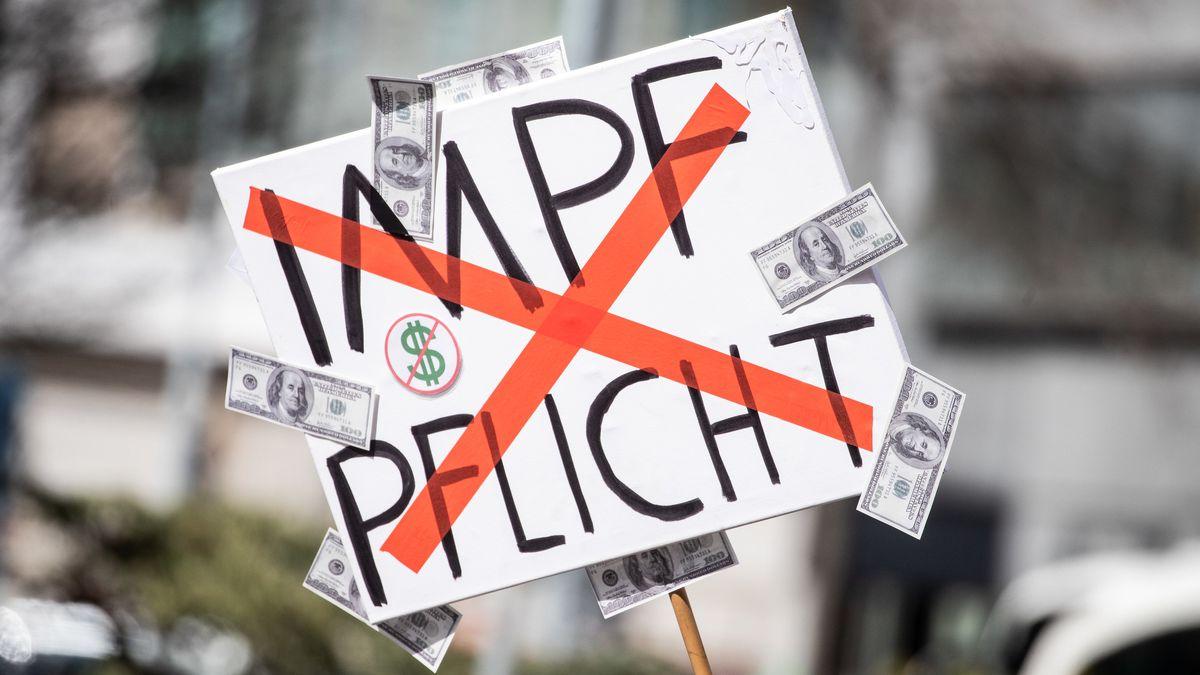 """Ein Mann trägt auf einer Demonstration der Initiative """"Querdenken"""" ein Schild mit einem durchgestrichenen """"Impflicht""""-Schriftzug."""