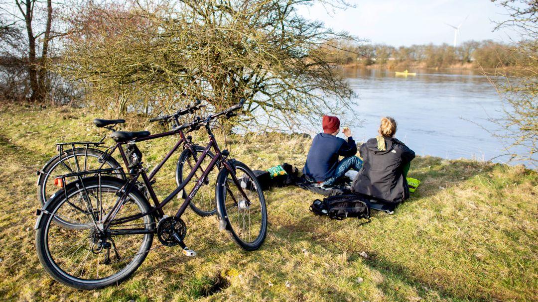 Fahrradfahrer sitzen am Ufer