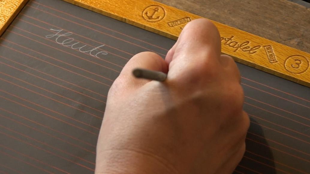 Eine Frau schreibt auf einer Schiefertafel