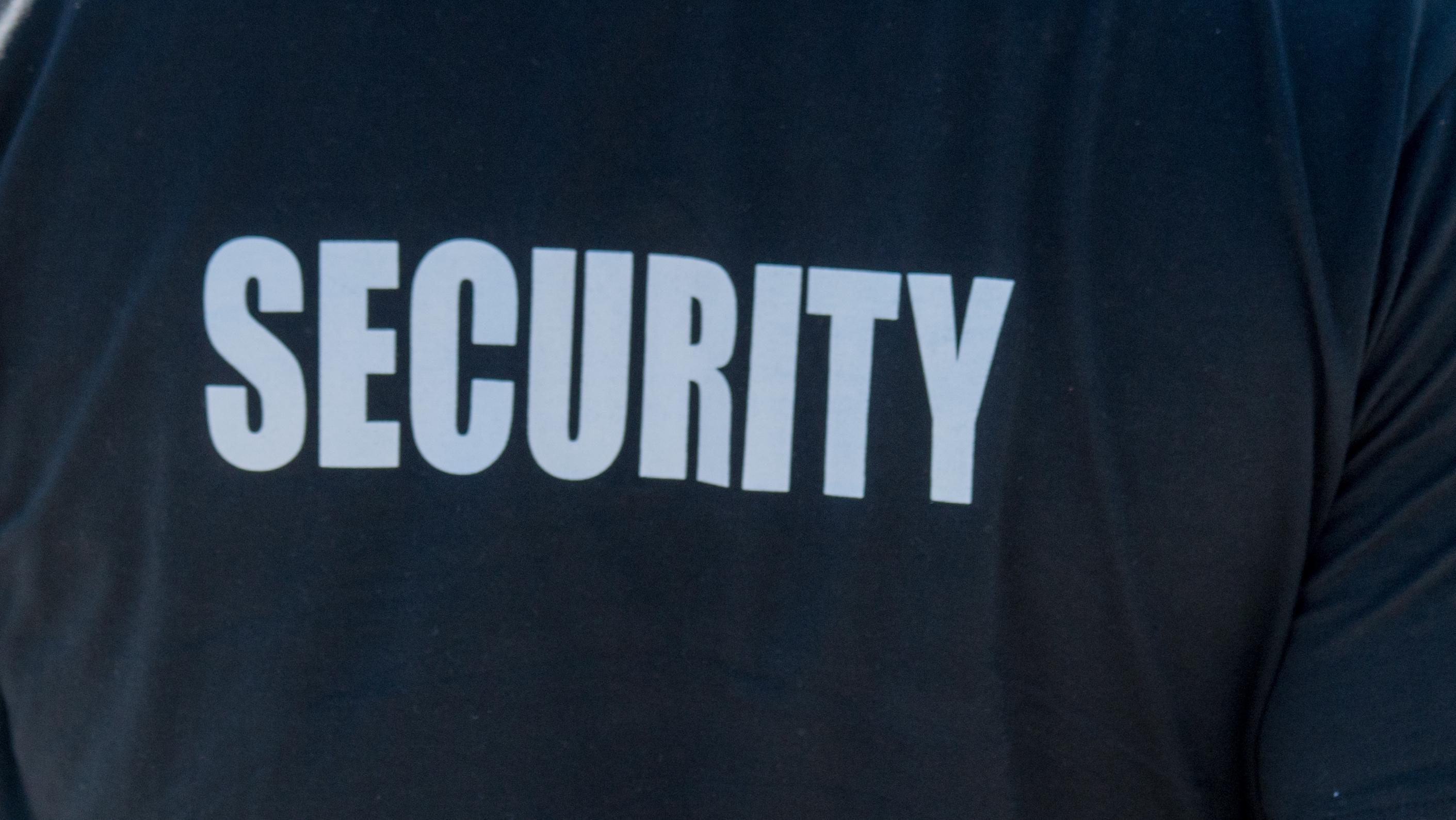 """Symbolbild: Weißer Schriftzug """"Security"""" auf dem Rücken eines schwarzen T-Shirts"""