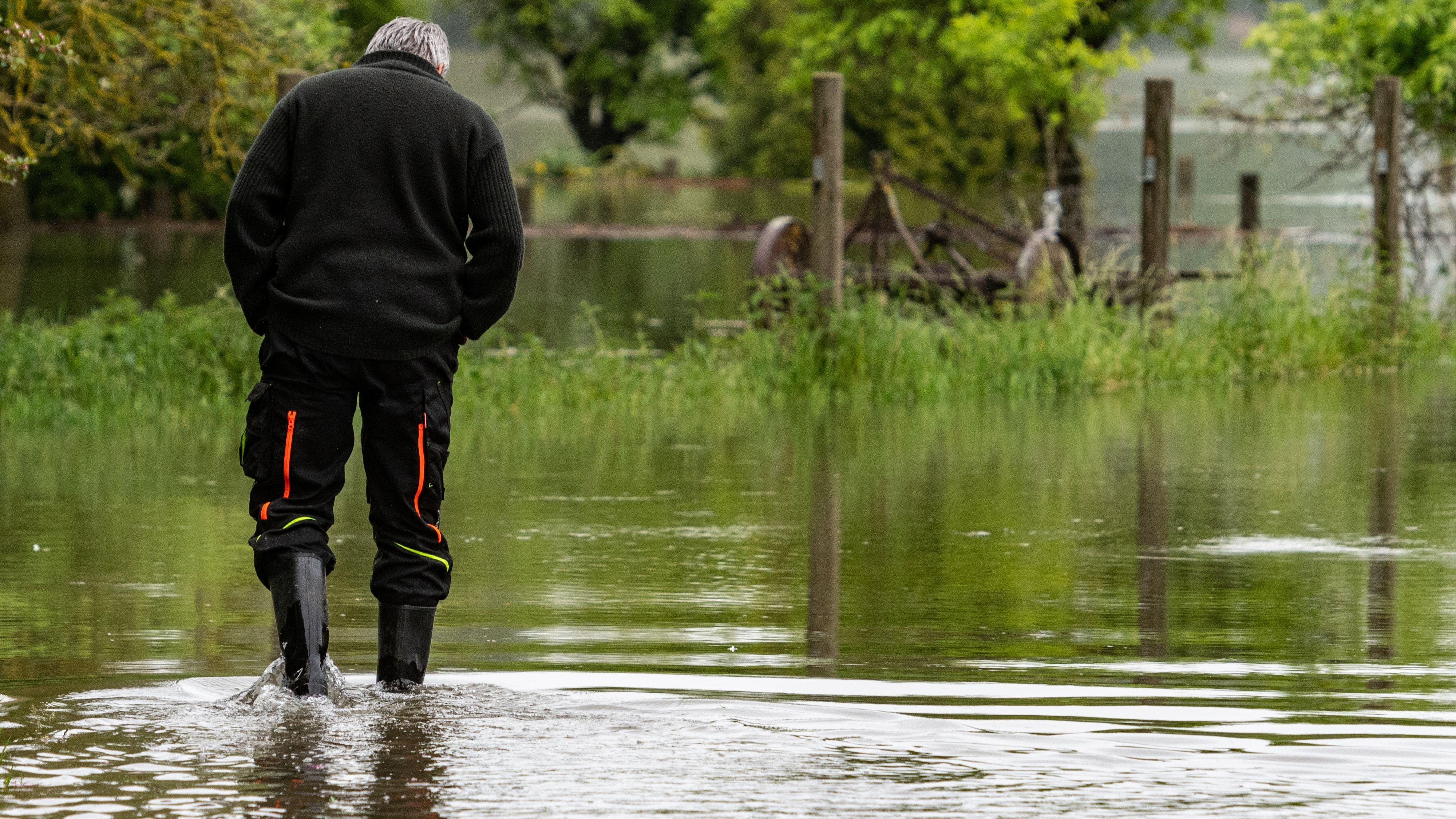 Ein Mann geht in Staubing im Landkreis Kelheim auf einer von der Donau überflutete Straße.